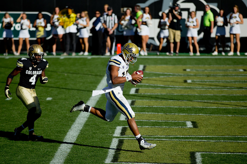 . BOULDER, CO - OCTOBER 25:  Quarterback Brett Hundley #17 of the UCLA Bruins strides into the end zone to score the game winning touchdown past defensive back Chidobe Awuzie #4 of the Colorado Buffaloes during double overtime at Folsom Field on October 25, 2014 in Boulder, Colorado. The Bruins defeated the Buffaloes 40-37 in double overtime. (Photo by Justin Edmonds/Getty Images)