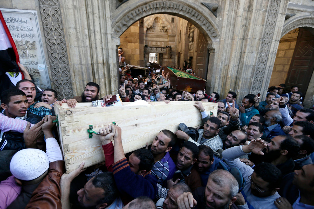 "Description of . Muslim Brotherhood and Egyptian President Morsi supporters carry two bodies who were killed during Wednesday\'s clashes during their funeral outside Al Azhar mosque, the highest Islamic Sunni institution, Friday, Dec. 7, 2012. During the funeral, thousands Islamist mourners chanted, ""with blood and soul, we redeem Islam,\"" pumping their fists in the air. \""Egypt is Islamic, it will not be secular, it will not be liberal,\"" they chanted as they walked in a funeral procession that filled streets around Al-Azhar mosque. Thousands of Egyptians took to the streets after Friday midday prayers in rival rallies and marches across Cairo, as the standoff deepened over what opponents call the Islamist president\'s power grab, raising the specter of more violence. (AP Photo/Hassan Ammar)"