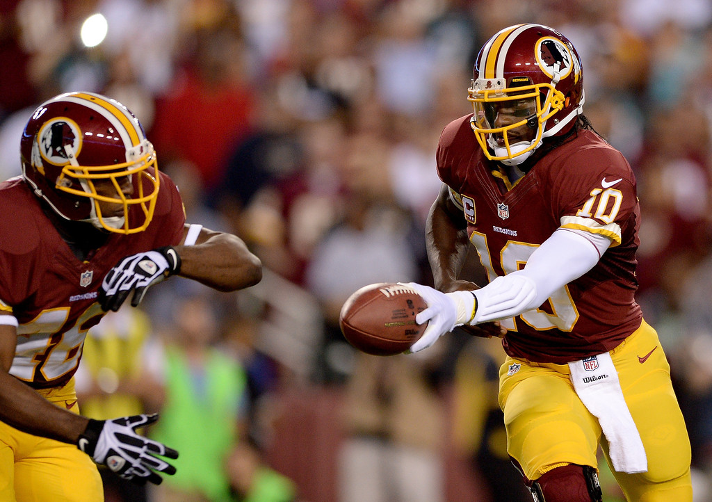 . Quarterback Robert Griffin III #10 of the Washington Redskins hands the ball off to running back Alfred Morris #46 before Morris fumbles in the first quarter against the Philadelphia Eagles at FedExField on September 9, 2013 in Landover, Maryland.  (Photo by Patrick Smith/Getty Images)