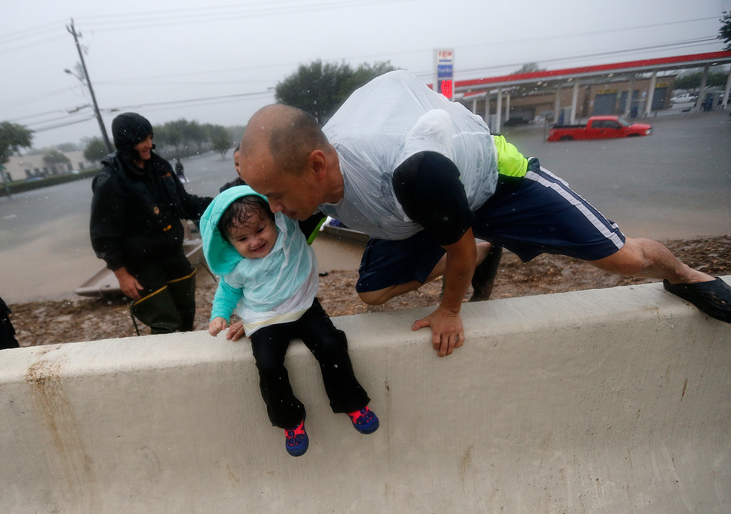 . Vinh Nguyen rests his daughter Kailie, 18 months, as he hops over a highway divider after being rescued in boats by the Louisiana Department of Wildlife and Fisheries, during flooding from Tropical Storm Harvey, which hit Texas last week as a Category 4 hurricane in Houston, Monday, Aug. 28, 2017. (AP Photo/Gerald Herbert)