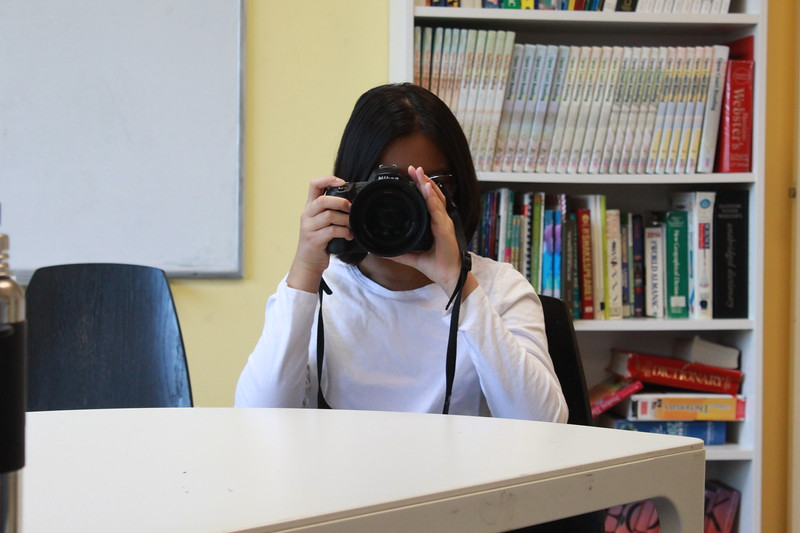 Suhani taking a photo in photography class.