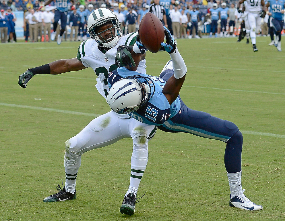 . Tennessee Titans wide receiver Justin Hunter (15) catches a 16-yard touchdown pass as he is defended by New York Jets cornerback Darrin Walls (30) in the second quarter of an NFL football game on Sunday, Sept. 29, 2013, in Nashville, Tenn.  (AP Photo/Mark Zaleski)