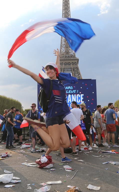 . A supporter of the French soccer team jumps in front of the Eiffel Tower after France won the World Cup final between France and Croatia, Sunday, July 15, 2018 in Paris. France won its second World Cup title by beating Croatia 4-2 . (AP Photo/Bob Edme)