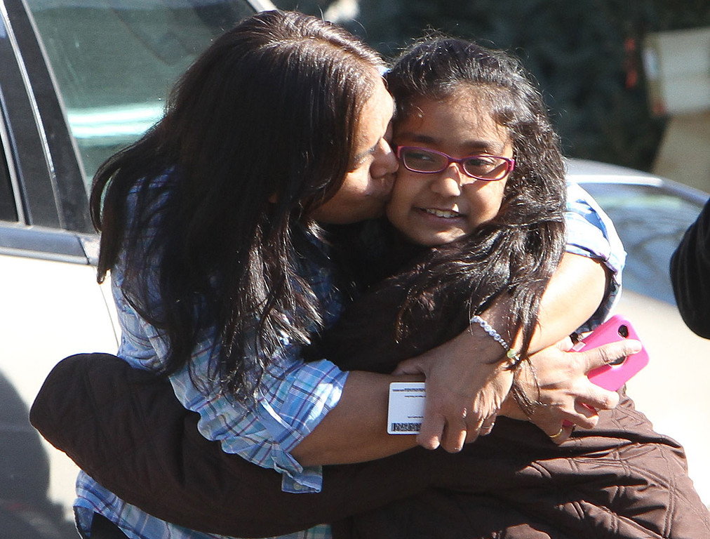 . A woman hugs her daughter after being reunited at the Sandy Hook firehouse after a mass shooting at the Sandy Hook Elementary School in Newtown, Conn. on Friday, Dec. 14, 2012. (AP Photo/The Journal News, Frank Becerra Jr.)