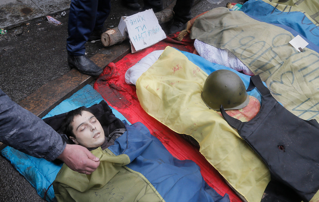 . A protesters shows the face of a victim killed in clashes with police in Kiev\'s Independence Square, the epicenter of the country\'s current unrest, Thursday, Feb. 20, 2014. (AP Photo/Efrem Lukatsky)