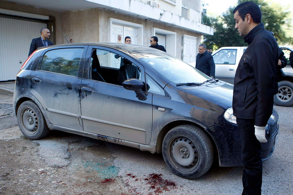 Description of . A forensic inspector (R) looks at the car of prominent Tunisian opposition politician Shokri Belaid, who was shot dead outside his home, in Tunis February 6, 2013. Belaid was shot dead outside his home on Wednesday, in a killing the prime minister condemned as a political assassination and a strike against the