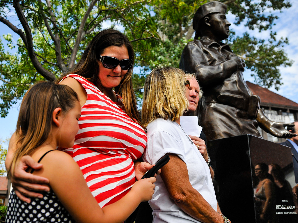 . Lynnette MacKay, wife of slain San Bernardino County Sheriff\'s Deputy Jeremiah MacKay, and daughter Kaitlyn share a moment together as they hold MacKay\'s beret while standing alongside MacKay\'s parents, Dawn and Alan MacKay, during the Jeremiah MacKay bronze statue dedication ceremony at the Lake Arrowhead Village in Lake Arrowhead on Sunday, Sept. 1, 2013. MacKay was killed on Feb. 12 in a gun battle with fugitive ex-cop Christopher Dorner near Big Bear during a massive manhunt in search of Dorner. (Rachel Luna / Staff Photographer)