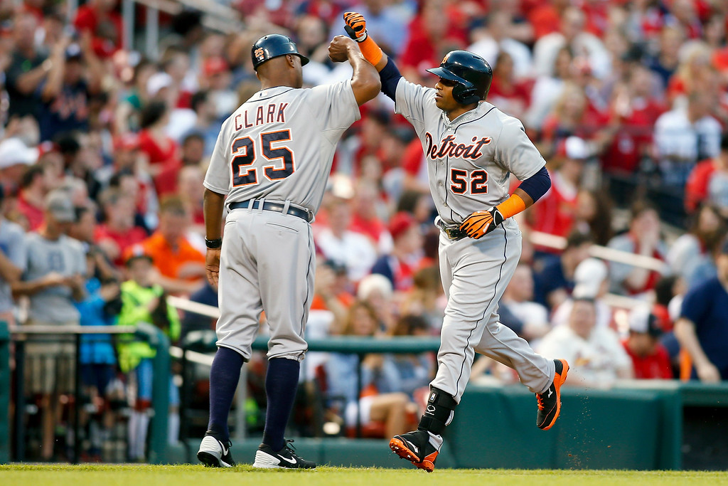 . Detroit Tigers third base coach Dave Clark, left, congratulates Yoenis Cespedes as he rounds the bases after hitting a solo home run during the second inning of a baseball game against the St. Louis Cardinals Friday, May 15, 2015, in St. Louis. (AP Photo/Scott Kane)