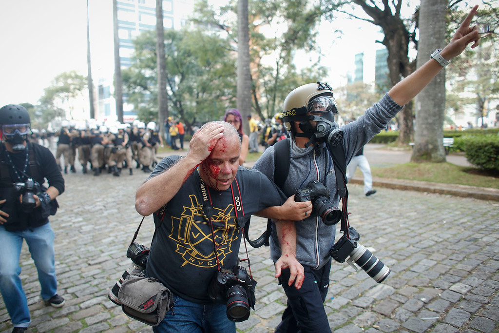 . Colleagues assist Reuters photographer Sergio Moraes, center, after being injured in the head with a rock during a protest against the 2014 World Cup in Belo Horizonte, Brazil, Thursday, June, 12, 2014.  (AP Photo/Victor R. Caivano)