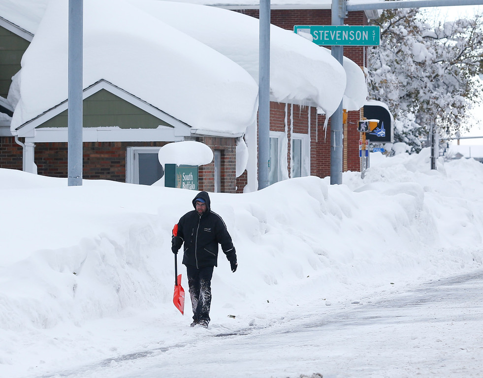 . A man carries a shovel as he walks in the south Buffalo area on Thursday, Nov. 20, 2014, in Buffalo, N.Y. A new blast of lake-effect snow pounded Buffalo for a third day piling more misery on a city already buried by an epic, deadly snowfall that could leave some areas with nearly 8 feet of snow on the ground when it\'s all done. (AP Photo/Mike Groll)
