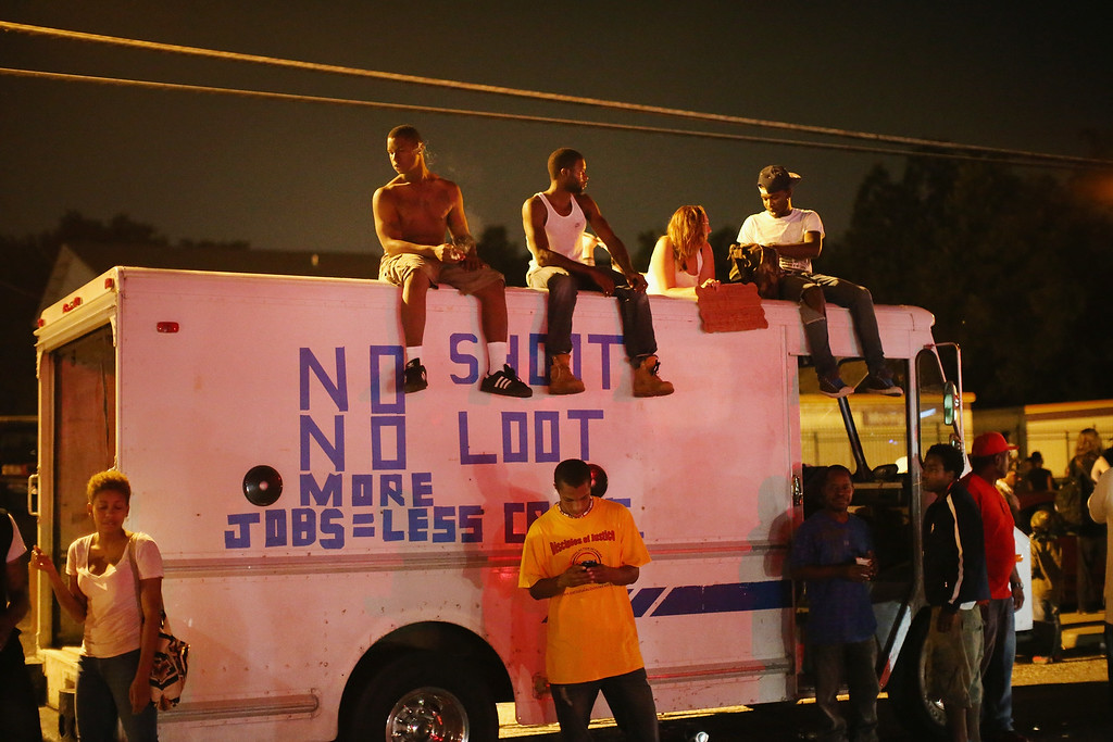 . Demonstrators protest the killing of teenager Michael Brown on August 17, 2014 in Ferguson, Missouri.  Despite the Brown family\'s continued call for peaceful demonstrations, violent protests have erupted nearly every night in Ferguson since his death. (Photo by Scott Olson/Getty Images)