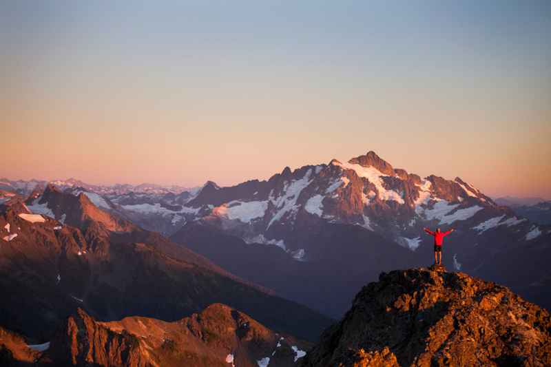 A hiker stands on a rocky ridge in North Cascades National Park.