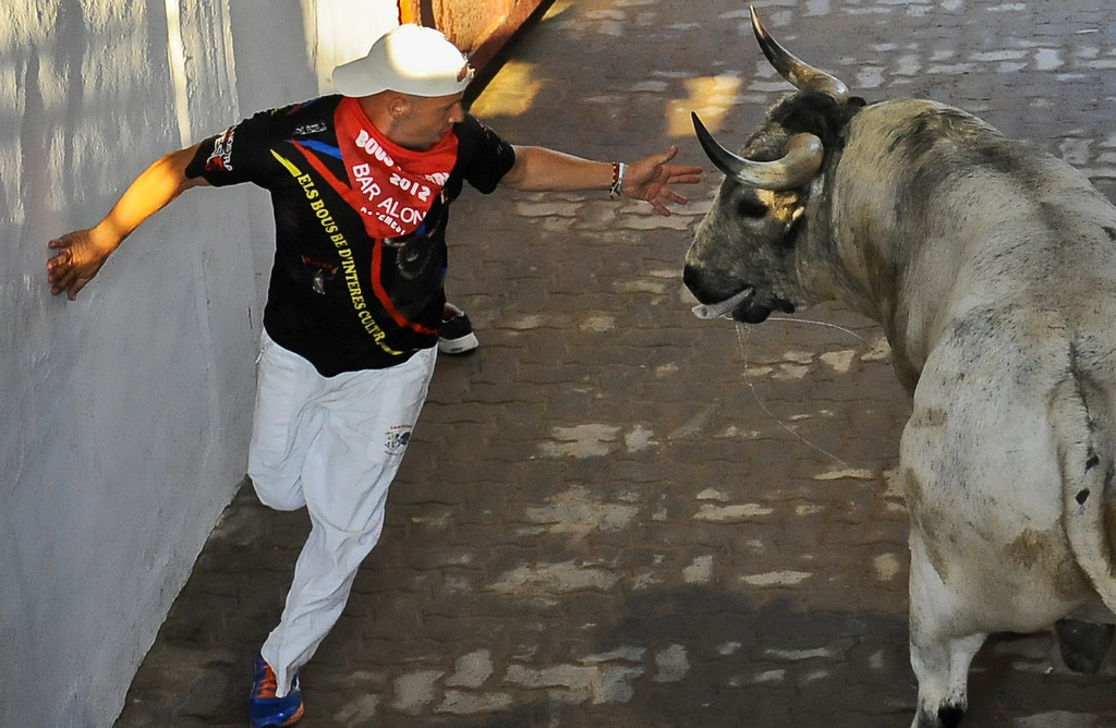 . A reveler flees from a Torrestrella\' ranch bull during the fifth running of the bulls at the San Fermin fiestas, in Pamplona northern Spain on Thursday, July 11, 2013. (AP Photo/Alvaro Barrientos)