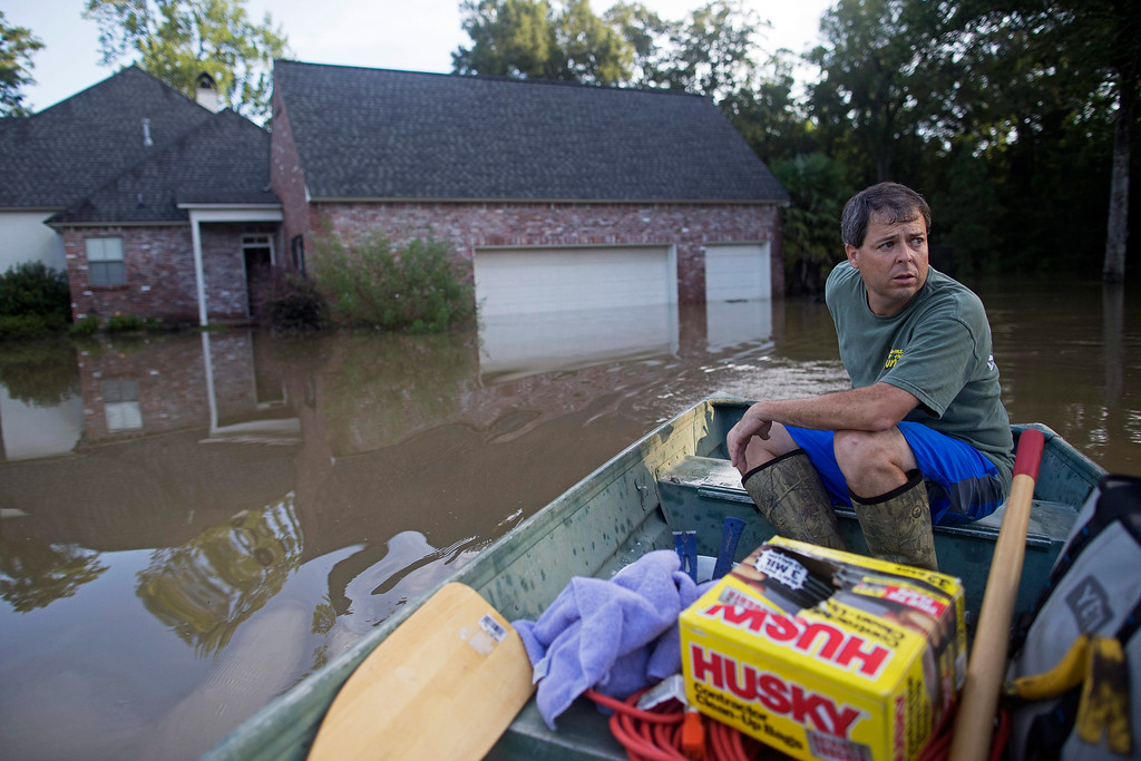 . David Key boats away from his flooded home after reviewing the damage in Prairieville, La., Tuesday, Aug. 16, 2016. Key, an insurance adjuster, fled his home as the flood water was rising with his wife and three children and returned today to assess the damage. (AP Photo/Max Becherer)