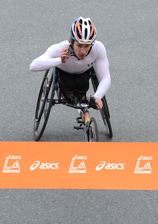 . 2014 ASICS LA Marathon men\'s wheelchair winner Joshua George crosses the finish line in Santa Monica Calif, with a time of 1: 33: 11.   Sunday, March 9,  2014.   (Photo by Stephen Carr / Daily Breeze)