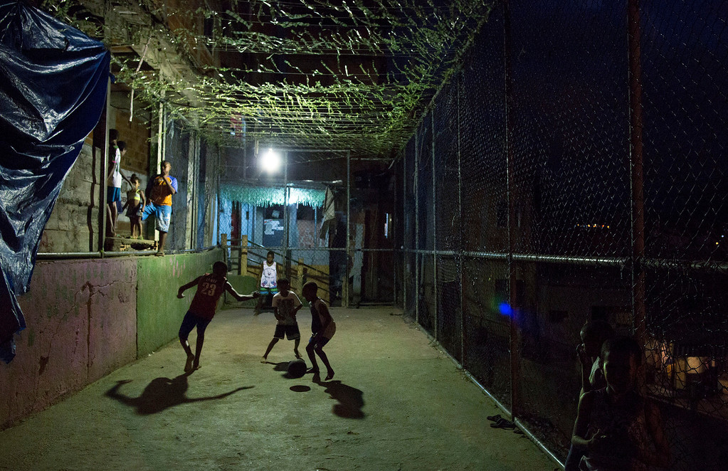 . In this Monday, June 2, 2014 photo, youth play soccer in the Mangueira slum of Rio de Janeiro, Brazil. �I would like to watch a final match between Brazil and Portugal because I�m a fan of Brazil�s Neymar and Portugal�s Cristiano Ronaldo,� said 13-year-old Alex Silva, a Mangueira resident. �But I know I won�t get to because I don�t have money to buy a ticket.� (AP Photo/Leo Correa)