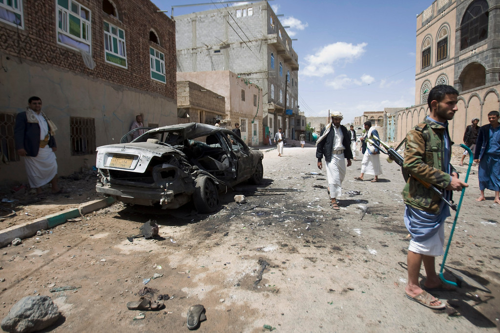 . Shiite rebels, known as Houthis, stand near a damaged car after a bomb attack in Sanaa, Yemen, Friday, March 20, 2015. Triple suicide bombers hit a pair of mosques crowded with worshippers in the Yemeni capital, Sanaa, on Friday, causing heavy casualties, according to witnesses. The attackers targeted mosques frequented by Shiite rebels, who have controlled the capital since September. (AP Photo/Hani Mohammed)
