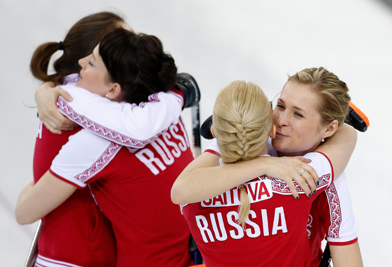 . Russia\'s Margarita Fomina, far right, kisses teammate Alexandra Saitova, while skip Anna Sidorova and Ekaterina Galkin hug at left, after defeating the United States during women\'s curling competition at the 2014 Winter Olympics, Tuesday, Feb. 11, 2014, in Sochi, Russia. (AP Photo/Robert F. Bukaty)