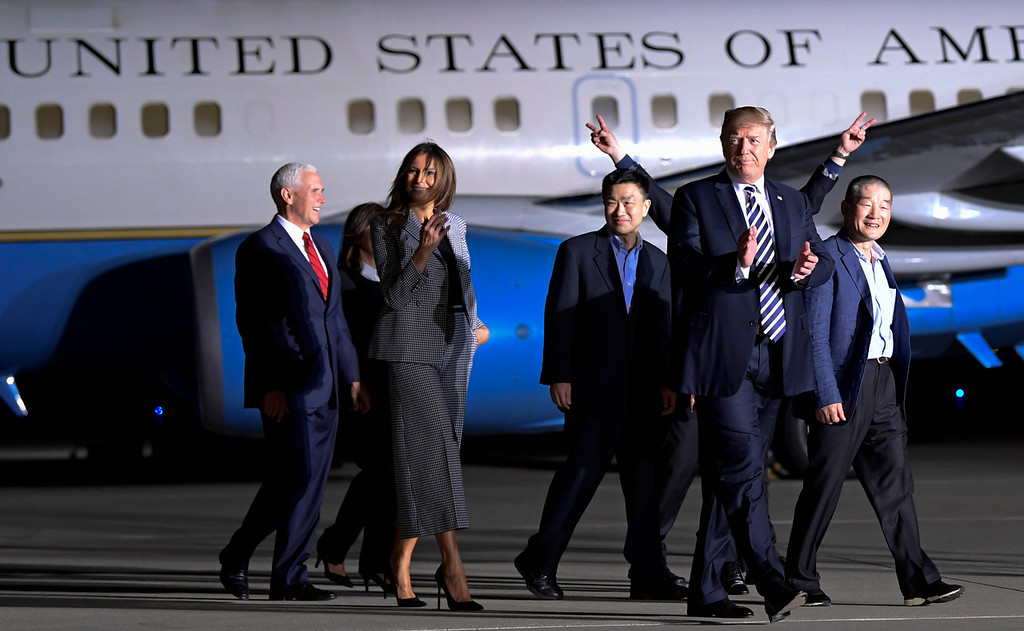 . President Donald Trump walks with Tony Kim, third right, Kim Dong Chul, right, and Kim Hak Song, behind Trump, the three Americans detained in North Korea for more than a year as they arrive at Andrews Air Force Base in Md., Thursday, May 10, 2018. Walking with Trump is Vice President Mike Pence, left, and first lady Melania Trump. (AP Photo/Susan Walsh)