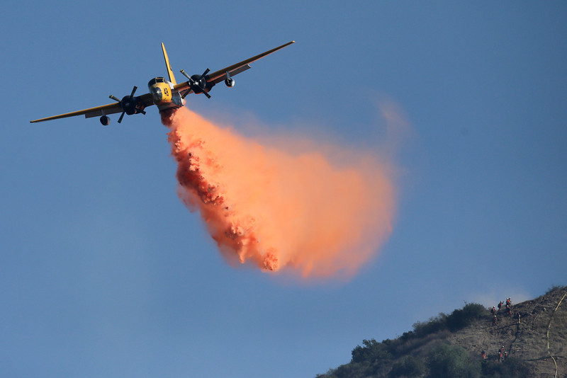 . An aircraft drops fire retardant on the Colby Fire on Friday, Jan. 17, 2014, near Azusa, Calif. Firefighters were chasing flare-ups Friday morning in the damaging wildfire that was largely tamed but kept thousands of people from their homes in the foothill suburbs northeast of Los Angeles.(AP Photo/Jae C. Hong)