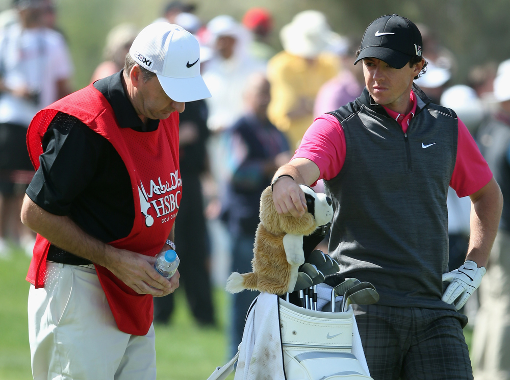 Description of . Rory McIlroy of Northern Ireland and his caddie JP Fitzgerald look dejected during the first round of The Abu Dhabi HSBC Golf Championship at Abu Dhabi Golf Club on January 17, 2013 in Abu Dhabi, United Arab Emirates.  (Photo by Andrew Redington/Getty Images)