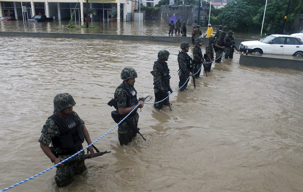 . Mexican Navy members secure a flooded area to prevent theft and robbery in Acapulco, Guerrero state, Mexico, after heavy rains hit the area on September 16, 2013. Hurricane Ingrid weakened to tropical storm strength as it made landfall on the northeastern coast in the morning while the Pacific coast was reeling from the remnants of Tropical Storm Manuel, which dissipated after striking on the eve. Thousands of people were evacuated on both sides of the country as the two storms set off landslides and floods that damaged bridges, roads and homes.   STR/AFP/Getty Images