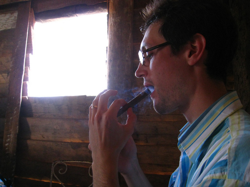 At a farmer's house where Mat's smoking a homemade cigar dipped in honey and sprayed with vanilla and rum