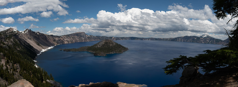 14 Aug 19	   Our last destination on the trip was to visit Crater Lake. Jan had never been there prior and I don't recall if I had ever been there as a child, but if so I don't remember it. This will be the first shot I share of it and it is a pano taken from what may be a location close to nine o'clock on the loop road circumnavigating the entire rim. We had access to roughly 1/4 of the road as the rest was still under snow. Not sure how much was remaining but we heard one of the rangers saying that the average snowfall was roughly 44 feet and they had received a little more this past year. I'll write more as I share additional shots.  This is a 9 pane pano which I've not altered at all save obviously for the combining of the images. Pano Overlook  Nikon D500; 18 - 200; Aperture Priority; ISO 200; 1/640 sec @ f /11.