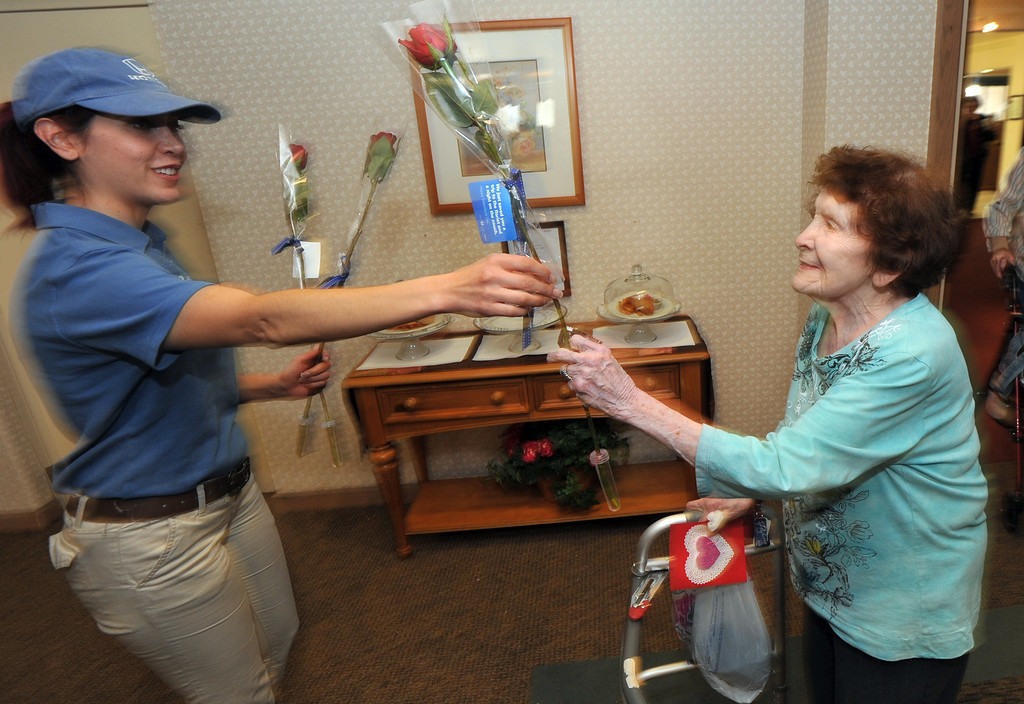. Tamara Torres, with Honda, gives resident, Ida Gomez, a receive long-stem red rose on Valentine\'s Day at Merill Gardens in Whittier on Thursday February 14, 2013. The Helpful Guys in Blue, a group sponsored by the Southern California Honda Dealers Association surprise Whittier residents with a complimentary red roses. (SGVN/Staff Photo by Keith Durflinger)