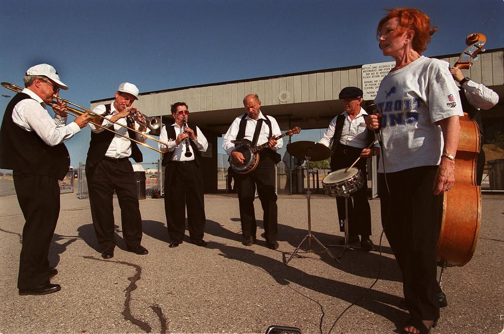 . Dixiebelle (Elma Santa) (right) dances as her band  The Dixie Jazz Cats play New Orleans jazz  tunes in front of the North Gate at the Pontiac Silverdome before Friday\'s Detroit Lions game against the Cincinnati Bengals.