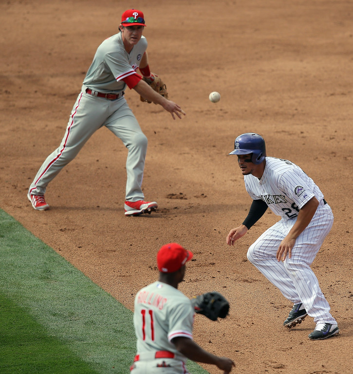 . Second baseman Chase Utley #26 of the Philadelphia Phillies and shortstop Jimmy Rollins #11 of the Philadelphia Phillies help run down Nolan Arenado #28 of the Colorado Rockies trying to steal second base to end the third inning at Coors Field on April 20, 2014 in Denver, Colorado.  (Photo by Doug Pensinger/Getty Images)