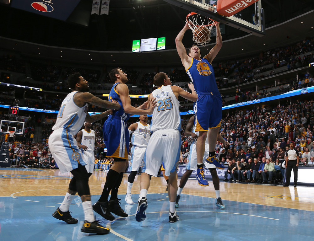 . Golden State Warriors forward David Lee, right, dunks the ball for a basket as, from left, Denver Nuggets forward Wilson Chandler, Warriors center Andrew Bogut, of Australia, and Nuggets center Timofey Mozgov, of Russia, look on in the first quarter of an NBA basketball game in Denver, Monday, Dec. 23, 2013. (AP Photo/David Zalubowski)