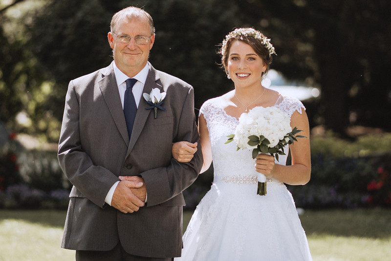 Bride smiles as her father walks her down the isle.