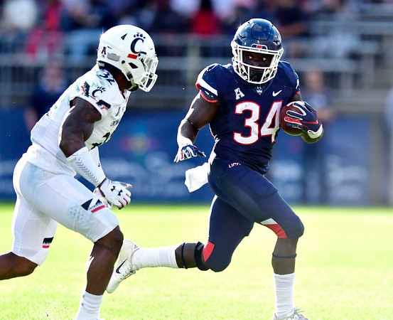 9/29/2018 Mike Orazzi | Staff UConn's Kevin Mensah (34) and Cincinnati's James Wiggins (32) during Saturday football game.