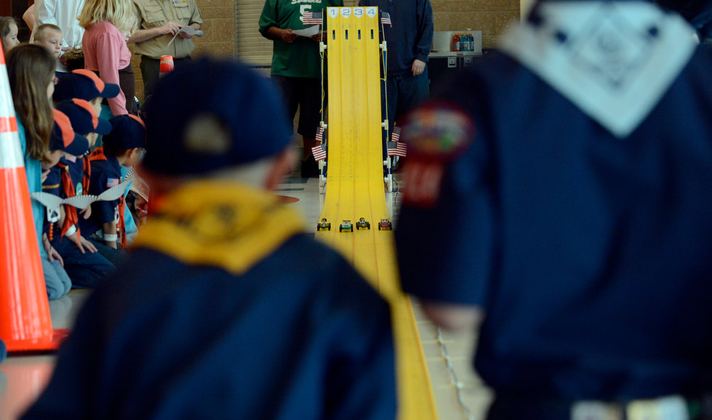 . COMMERCE CITY, CO. - JANUARY 26: Contestants watch their cars race down the track as they head to the finish line during the 2013 Pack 414 Pinewood Derby races at Ortho Stuart Middle School January 26, 2013 in Commerce City. The pinewood cars weigh 5 oz and are 7 inches long. The cars take about 3 second to go down the track.  The scouts can either buy a kit with the car already shaped or buy a block of wood and carve their own.  (Photo By John Leyba / The Denver Post)