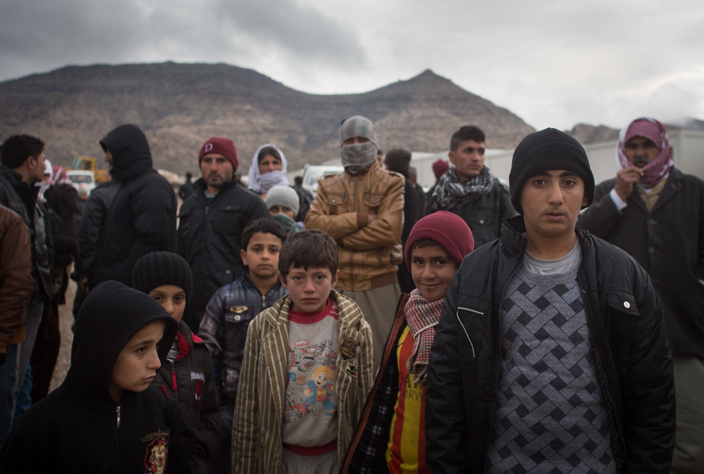 . Displaced Iraqis, who were forced to flee their home because of Islamic State\'s advance earlier this year, queue for humanitarian aid that is being distributed by the Barzani Charity Foundation after being delivered by lorries from the Polish charity SOS FOR LIFE at a refugee camp near Zakho on December 10, 2014 in Duhok, Iraq. Two articulated lorries that were driven from Poland full of blankets, winter clothes and children\'s cots delivered the aid to the camp that mainly houses Yazidis who, actively persecuted by ISIL, now live in hundreds of portable cabins.  Although the autonomous Kurdistan region in northern Iraq was already a refuge for an estimated 250,000 Syrian refugees, since the Islamic State began its onslaught on Iraq in June, Kurdistan has also taken in a more than one and a half million displaced people. Many have been placed in purpose-built refugee camps but the huge numbers and as winter in the region closes in, there are growing concerns for the welfare of the displaced persons who, while their homes are still in ISIL controlled territory, have no realistic prospect of returning to them.  (Photo by Matt Cardy/Getty Images)