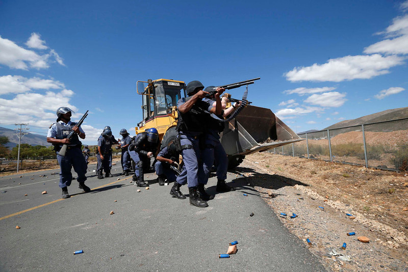 . Police fire on demonstrators during a farm workers strike at De Doorns on the N1 highway linking Cape Town and Johannesburg, January 10, 2013 . Police fired rubber bullets and stun grenades at hundreds of striking farm workers who blocked a highway in the grape-growing Western Cape on Thursday, the first clashes of a year likely to be marked by fractious labour relations.  Hundreds of striking workers seeking higher wages and better working conditions again blocked a major highway running through the town of De Doorns, about 100 kms (60 miles) east of Cape Town, hurling stones at motorists. REUTERS/Mike Hutchings