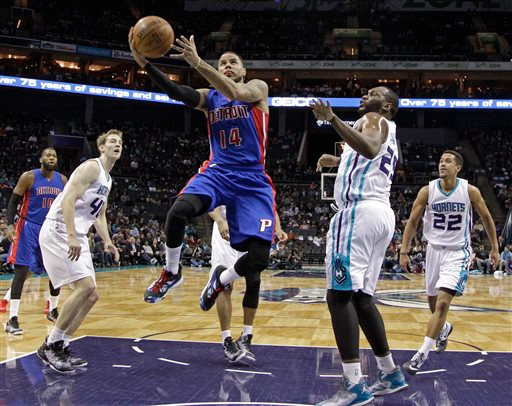 . Detroit Pistons\' D.J. Augustin (14) drives past Charlotte Hornets\' Al Jefferson (25) and Cody Zeller (40) during the first half of an NBA basketball game in Charlotte, N.C., Tuesday, Feb. 10, 2015. (AP Photo/Chuck Burton)