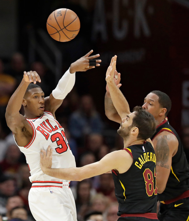 . Chicago Bulls\' Kris Dunn, left, throws a pass over Cleveland Cavaliers\' Channing Frye, back, and Jose Calderon, from Spain, during the first half of an NBA basketball game Thursday, Dec. 21, 2017, in Cleveland. (AP Photo/Tony Dejak)