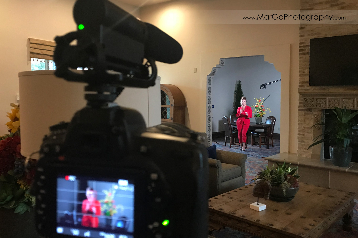 behind the scenes of indoor filming speaker in red suit - focus on woman standing in front of the table