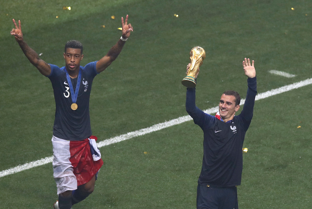 . France\'s Presnel Kimpembe, left, and Antoine Griezmann celebrate with the trophy at the end of the final match between France and Croatia at the 2018 soccer World Cup in the Luzhniki Stadium in Moscow, Russia, Sunday, July 15, 2018. (AP Photo/Thanassis Stavrakis)
