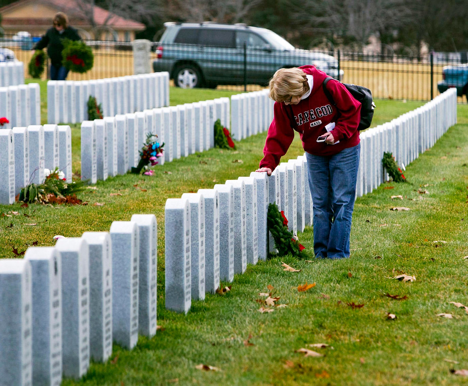 . Karen Comstock of Boise, pauses for a bit at the grave of her father David Hand, a veteran of the Korean War, after laying a wreath at his memorial, Saturday, Dec. 13, 2014, in Boise, Idaho. The Boise Civil Air Patrol and a small army of volunteers laid wreaths at the grave sites of 3,100 veterans Saturday following a ceremony at the Idaho State Veterans Cemetery in Boise. The event was part of the annual Wreaths Across America.  (AP Photo/The Idaho Statesman, Darin Oswald )