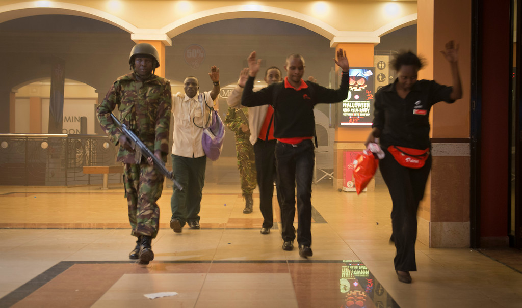 . Civilians who had been hiding during the gun battle hold their hands in the air as a precautionary measure before being searched by armed police leading them to safety, inside the Westgate Mall in Nairobi, Kenya Saturday, Sept. 21, 2013.  (AP Photo/Jonathan Kalan)