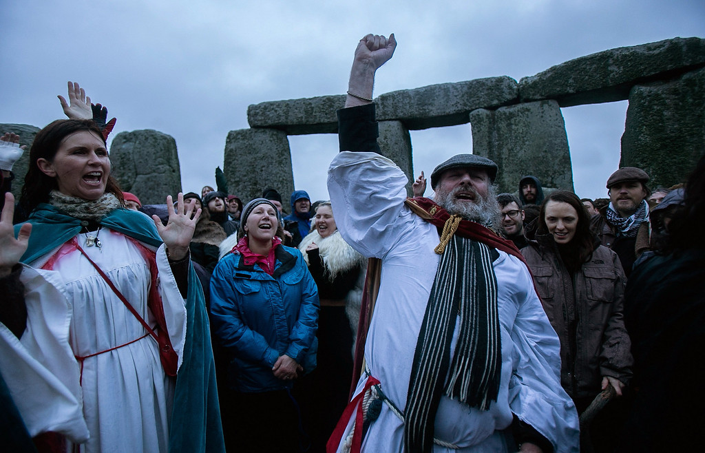 . Rollo Maughfling, Archdruid of Stonehenge & Britain, (R) conducts a ceremony as druids, pagans and revelers gather, hoping to see the sun rise as they take part in a winter solstice ceremony at Stonehenge on December 21, 2013 in Wiltshire, England. (Photo by Matt Cardy/Getty Images)