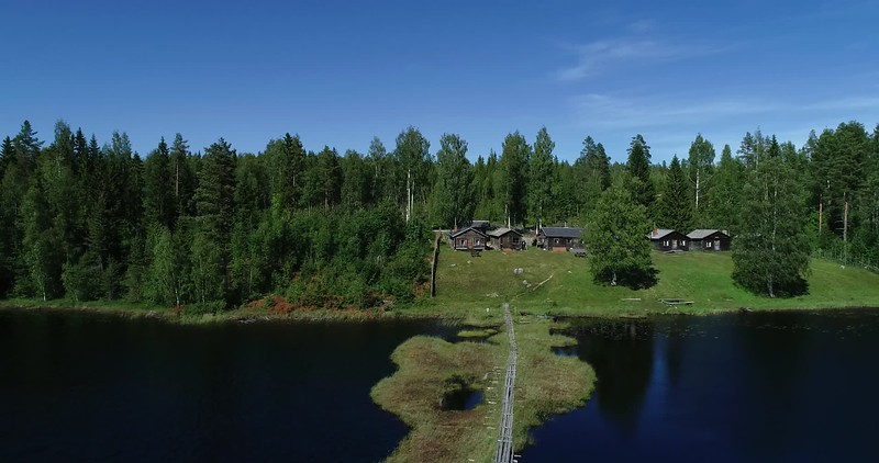 Aerial: 180 degrees panorama over a lake with a bridge to a hill farm