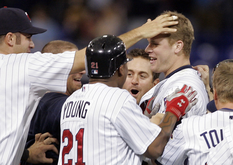 . The Twins\' Joe Mauer, left, gives a tap on the head to Justin Morneau after he drove in the winning run with a 10th inning single to lead the Twins to a 2-1 win over the Cleveland Indians on Sunday, April 20, 2008 in Minneapolis. (AP Photo/Jim Mone)