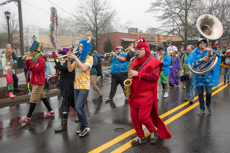 Matt Smith, in red,  plays his saxophone while marching during the 2018 Mead Rd. Mardi Gras parade.