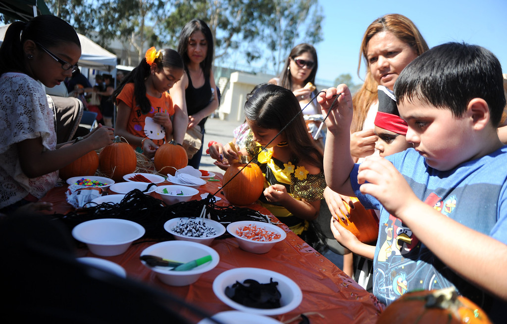. Kids and adults design pumpkins during the annual Open House and Haunted Jail at Norwalk Sheriff Station in Norwalk, Calif., on Saturday, Oct. 19, 2013. Sheriff department\'s Aero Bureau, SWAT, Arson Explosives Detail, Recruitment unit, along with the L.A. County Fire Department, U.S. Army with a military vehicle, CHP, and the Sheriff\'s Department dragster were on display.  (Keith Birmingham Pasadena Star-News)