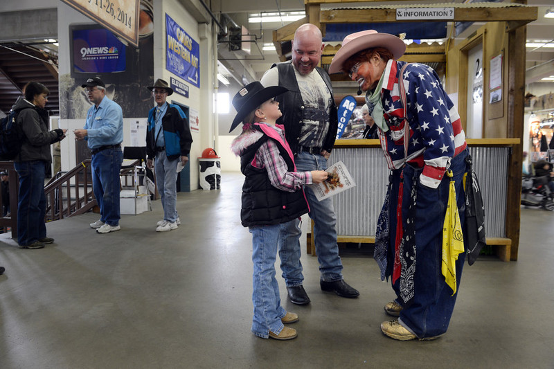 """. Duane Reichert greets Madison Buckridge, 7, and her grandfather Tony Newt at the National Western Stock Show in Denver, CO, January, 26, 2013. Reichert was inviting families to his one man act, Backstage with a Rodeo Clown. He says he\'s been a rodeo clown for 5 decades and started at age 19. Reichert used to get an adrenaline rush protecting cowboys from bulls he said, \""""now I get the same rush from making people laugh.\""""  (Photo By Craig F. Walker / The Denver Post)"""