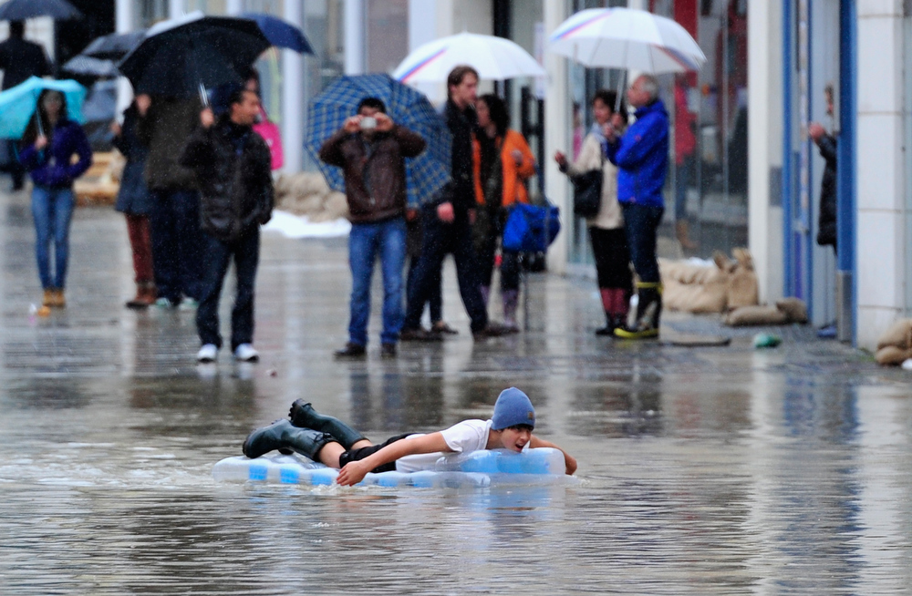 . A young man paddles on his inflatable mattress through the flooded streets in the historic city center on June 3, 2013 in Passau, Germany. Heavy rains are pounding southern and eastern Germany, causing wide-spread flooding and ruining crops. At least two people are missing and feared dead in what is evolving into the most serious flood levels since the so-called 100-year flood of 2002. Portions of Austria and the Czech Republic are also inundated.  (Photo by Lennart Preiss/Getty Images)